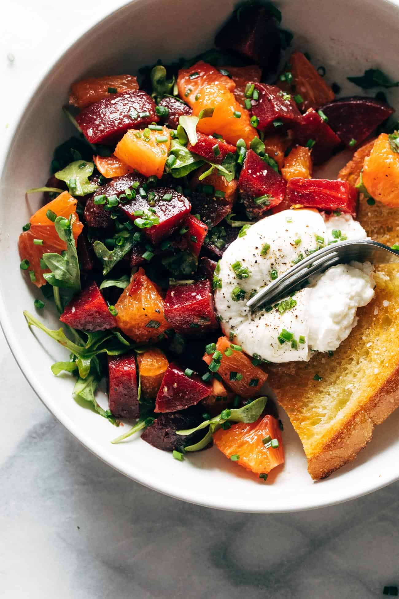 Beet and burrata salad in a bowl with fried bread and a fork