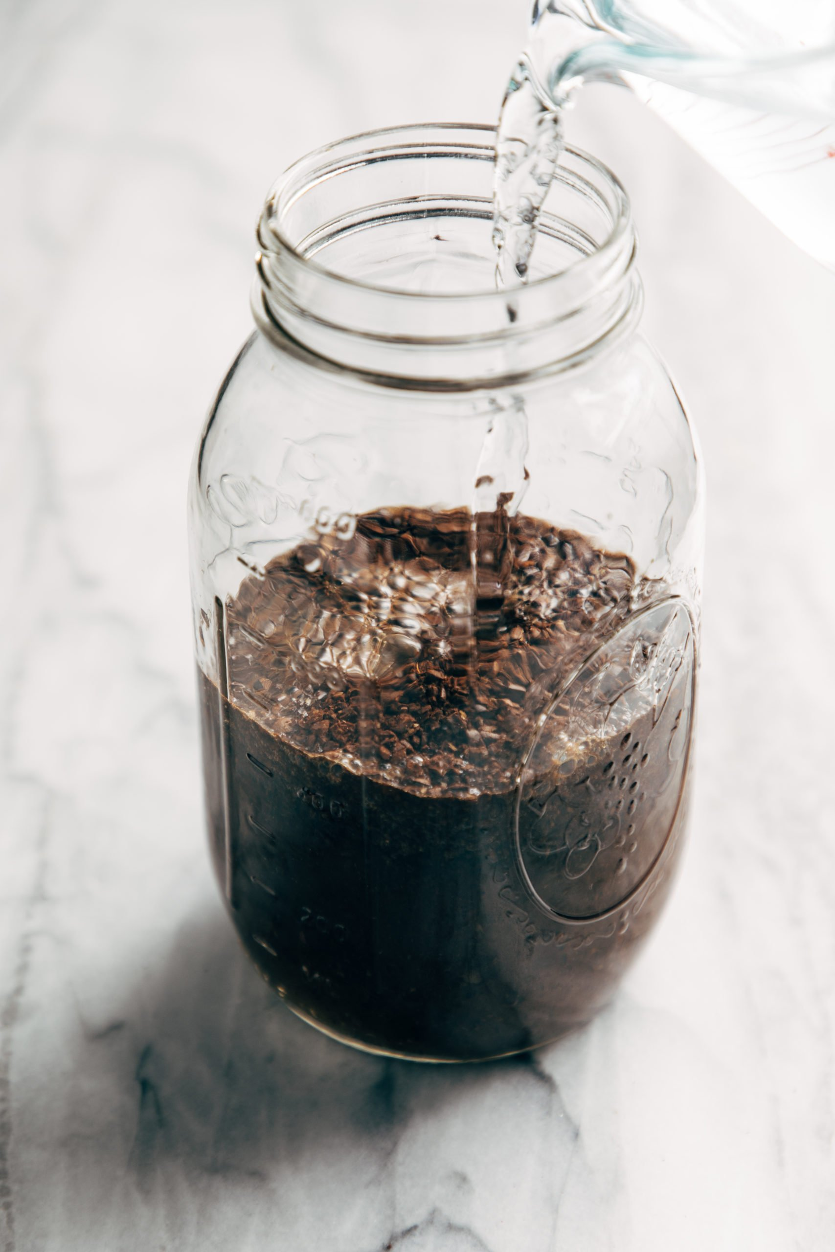 Water being poured over coffee grounds in a mason jar for cold brew coffee