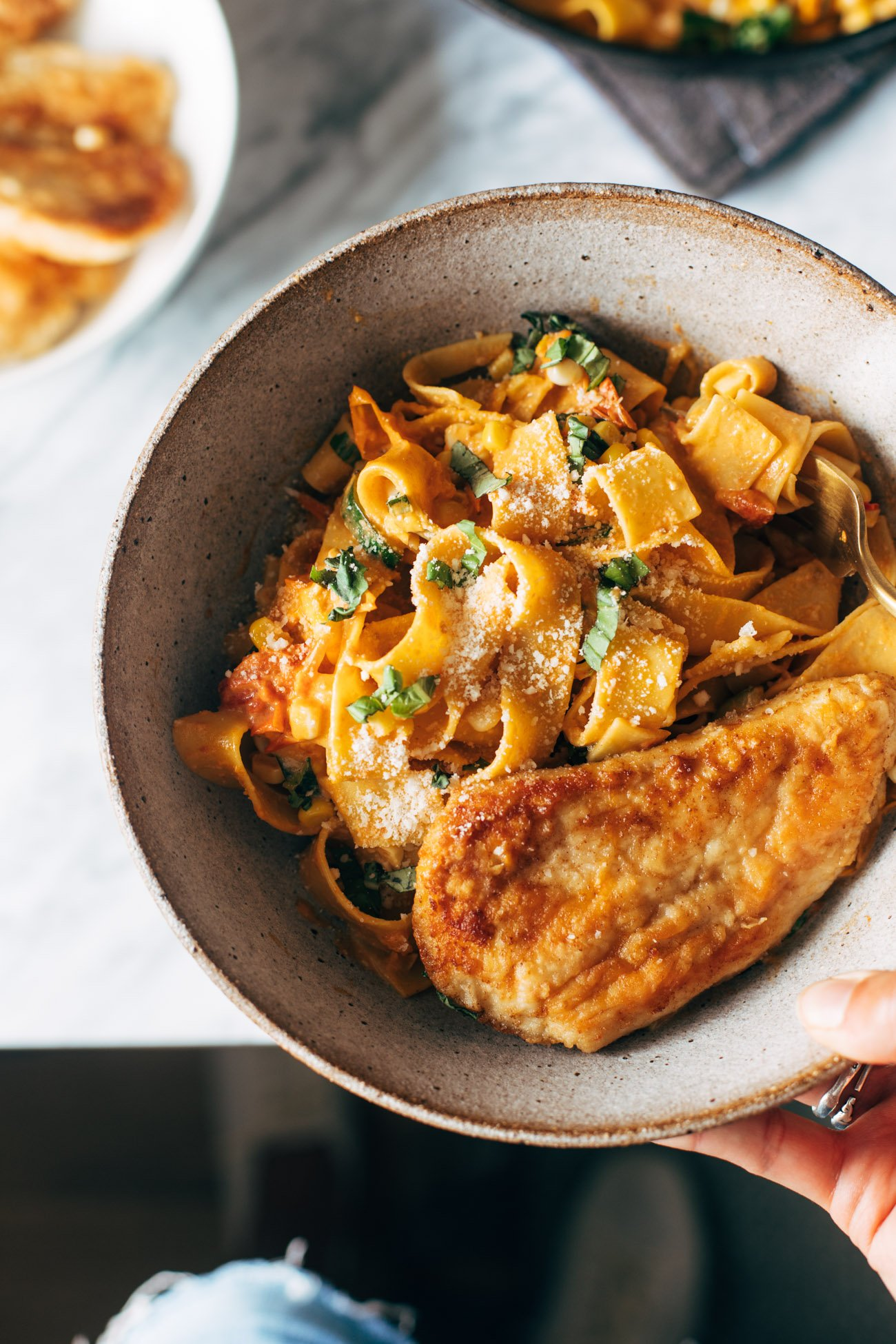 Burst tomato pappardelle in a bowl with a white hand holding the bowl. There's a pan-fried piece of chicken on top of the pasta.