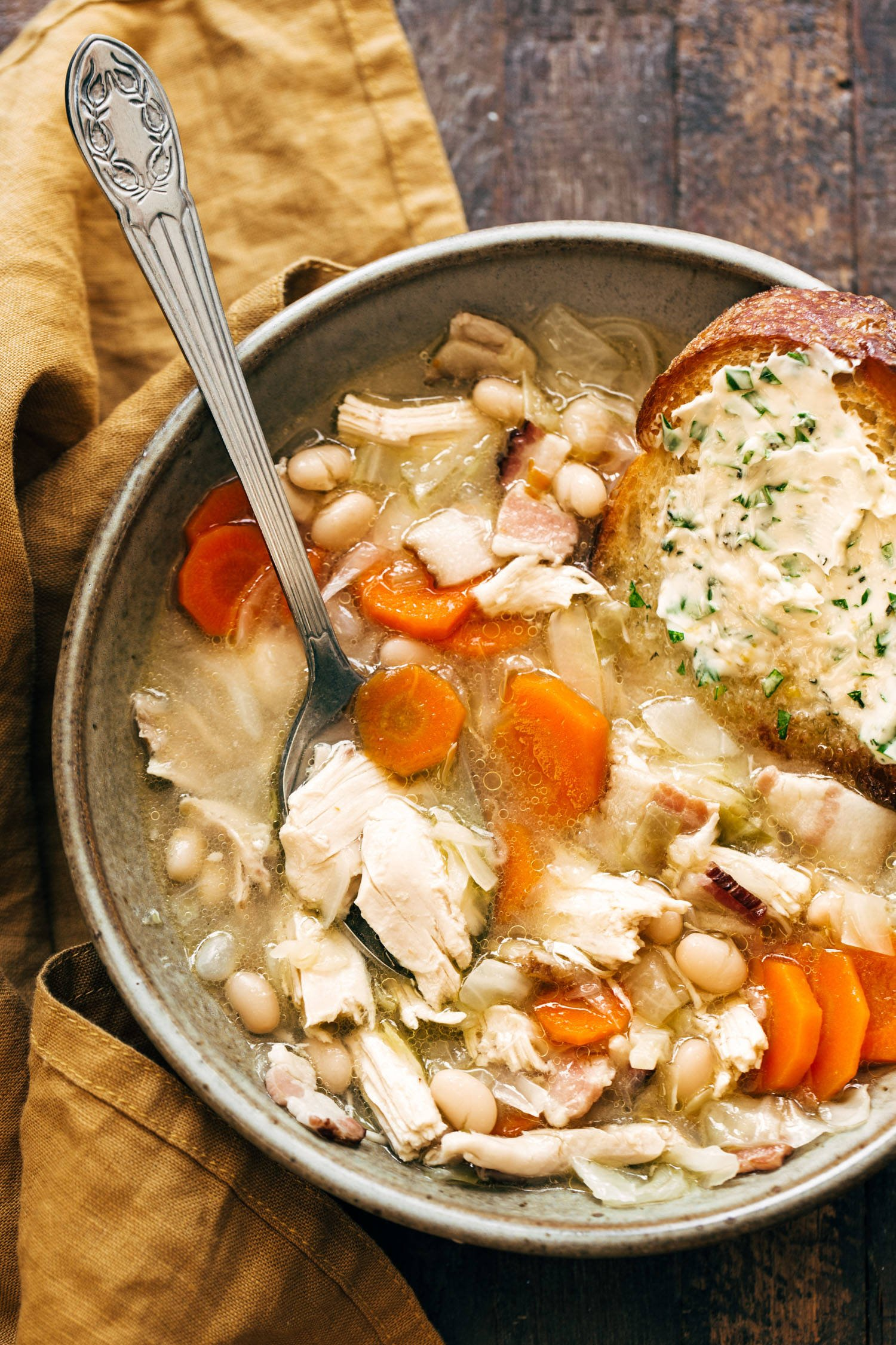 Chicken stew in a bowl with a spoon and garlic herb butter bread.